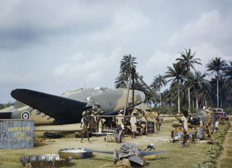 Local workers helping RAF fitters change the engine of a Lockheed Hudson at Yundum in the Gambia in April 1943