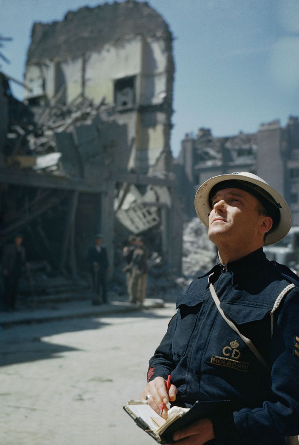 c. 1941 An Air Raid Precautions (ARP) warden inspects damaged buildings in Holborn, London.