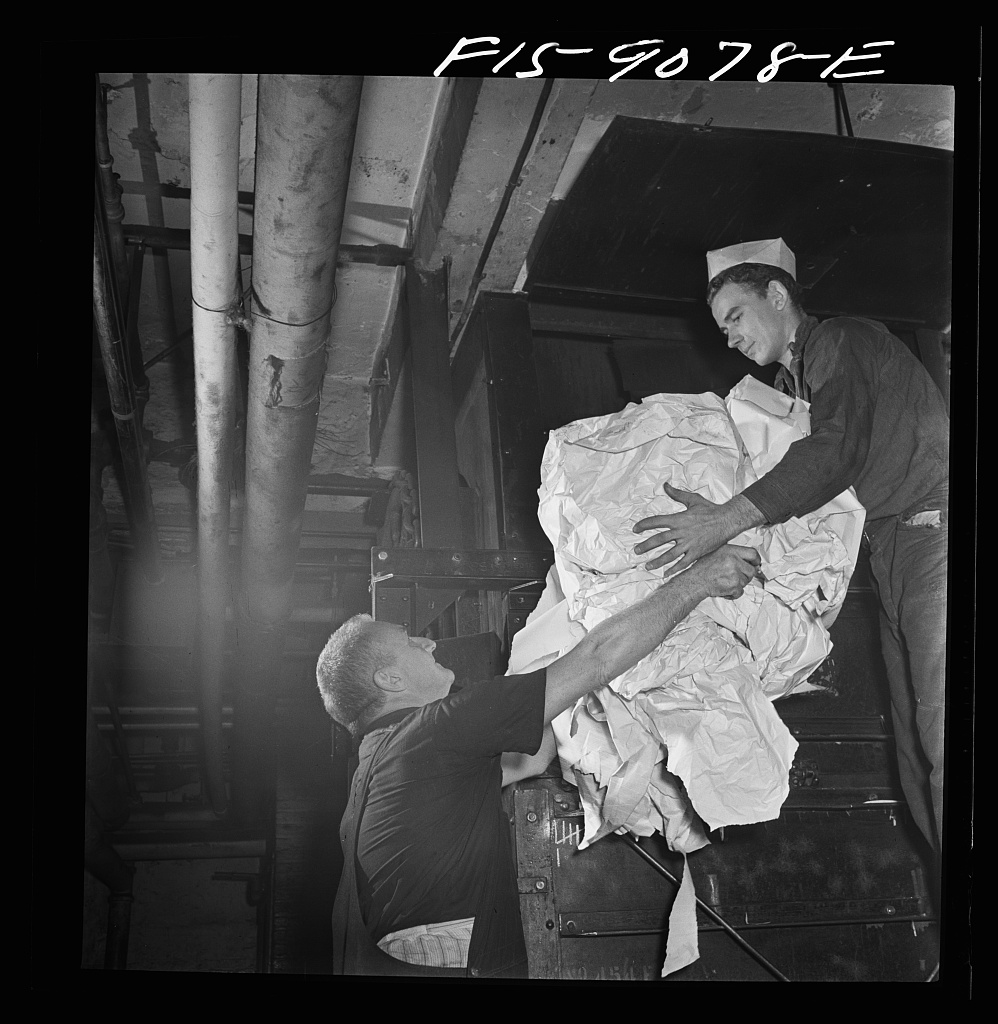"""Reel room of the New York Times newspaper. Waste paper is picked up off floor, placed in bins, baled and sold to the government for scrap. This young boy is an apprentice, or """"fly boy"""""""