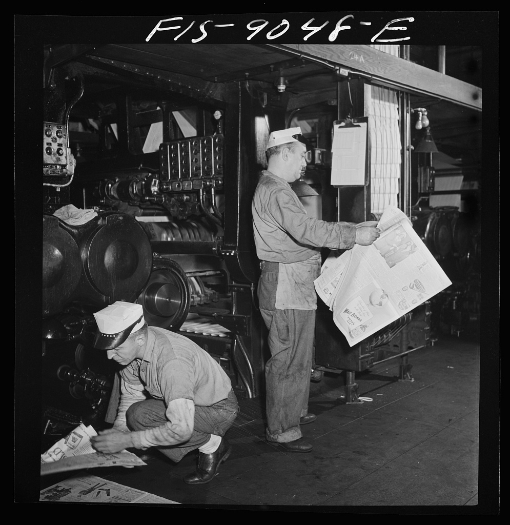 Pressroom of the New York Times newspaper. As presses are rollig and finished papers start coming off (see background), pressmen read the paper to catch defective press work. Pressman in foreground is filling ink fount