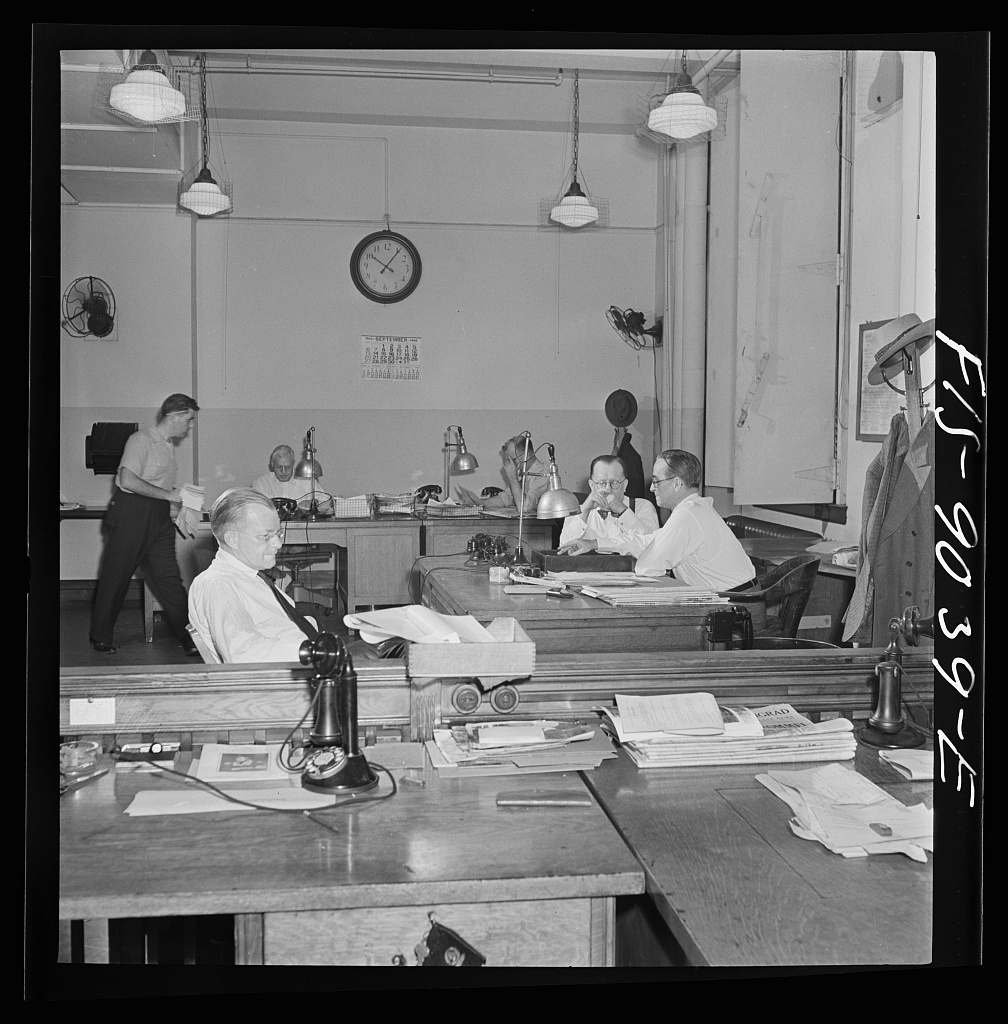 "Newsroom of the New York Times newspaper. The ""bull pen"" where managing editors and others sit at one side. In foreground, assistant managing editor Rae. In background, managing editor James and night managing editor McCaw conferring"