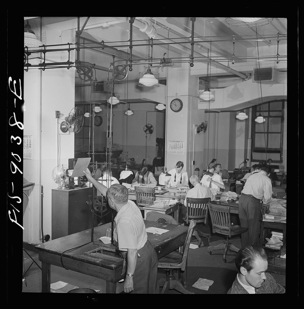 Newsroom of the New York Times newspaper. Ten o'clock is news room deadline. Copy is sent up to composing room on moving belt. Telegraph desk in background