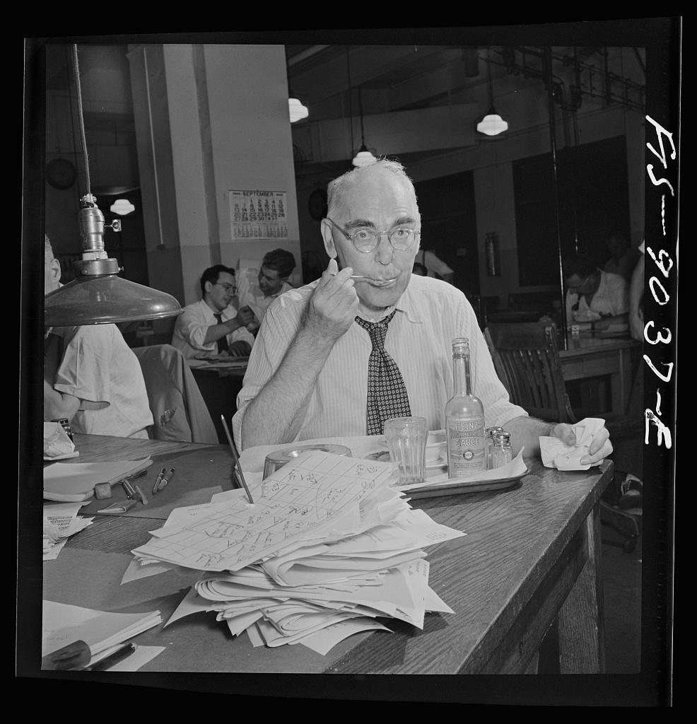 Financial desk copy reader on the New York Times newspaper staff has lunch on tray ordered from outside. Lunch in the news room is a half-hour period about 11 PM between editions
