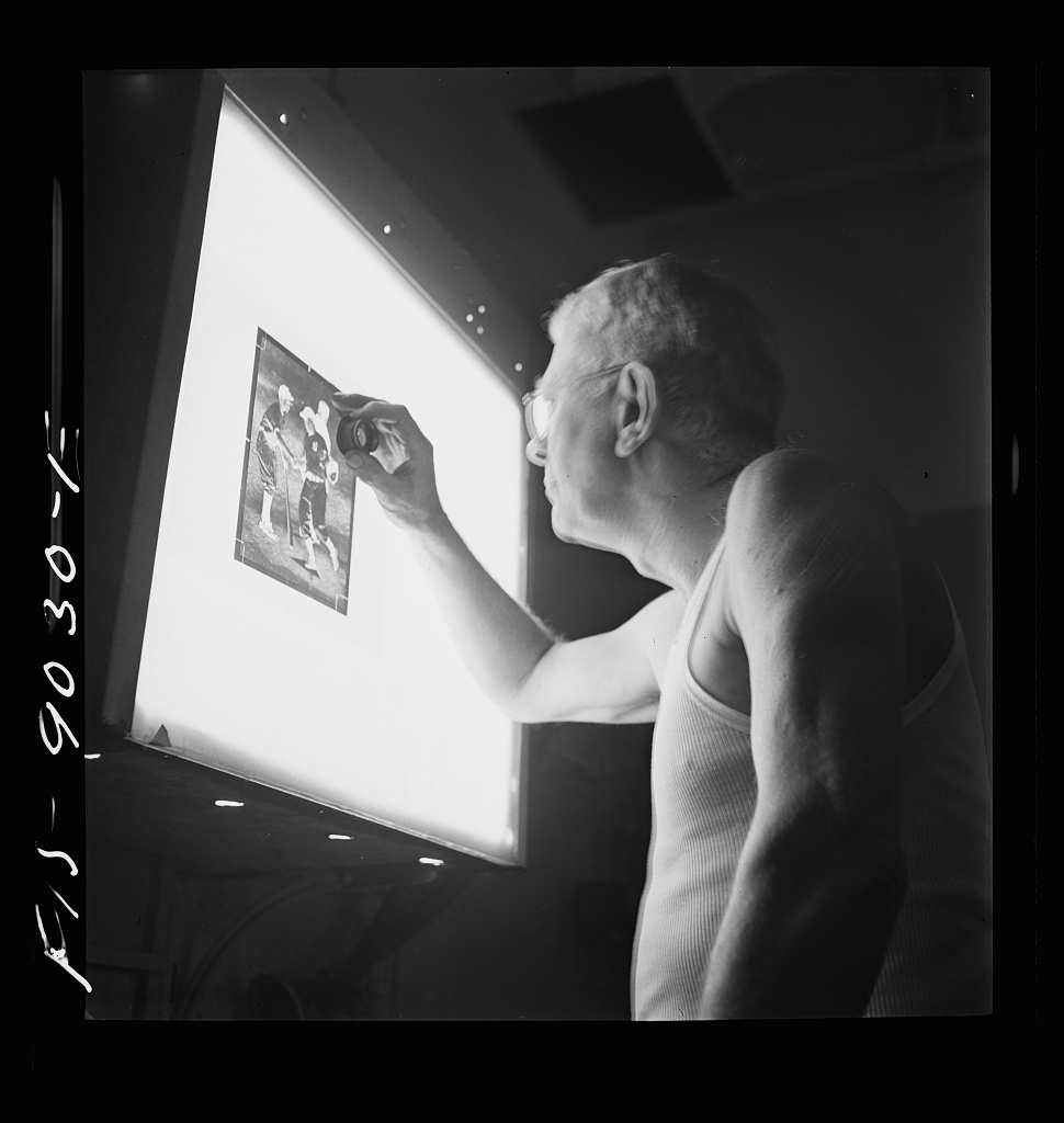 Photo engraving department of the New York Times newspaper. Examining the dots on the screen of a strip negative in the darkroom before it is transferred to a zinc plate