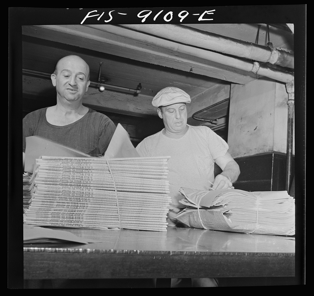 Mailroom of the New York Times newspaper. After arriving on a conveyor from the press room, papers are wrapped in bundles according to orders