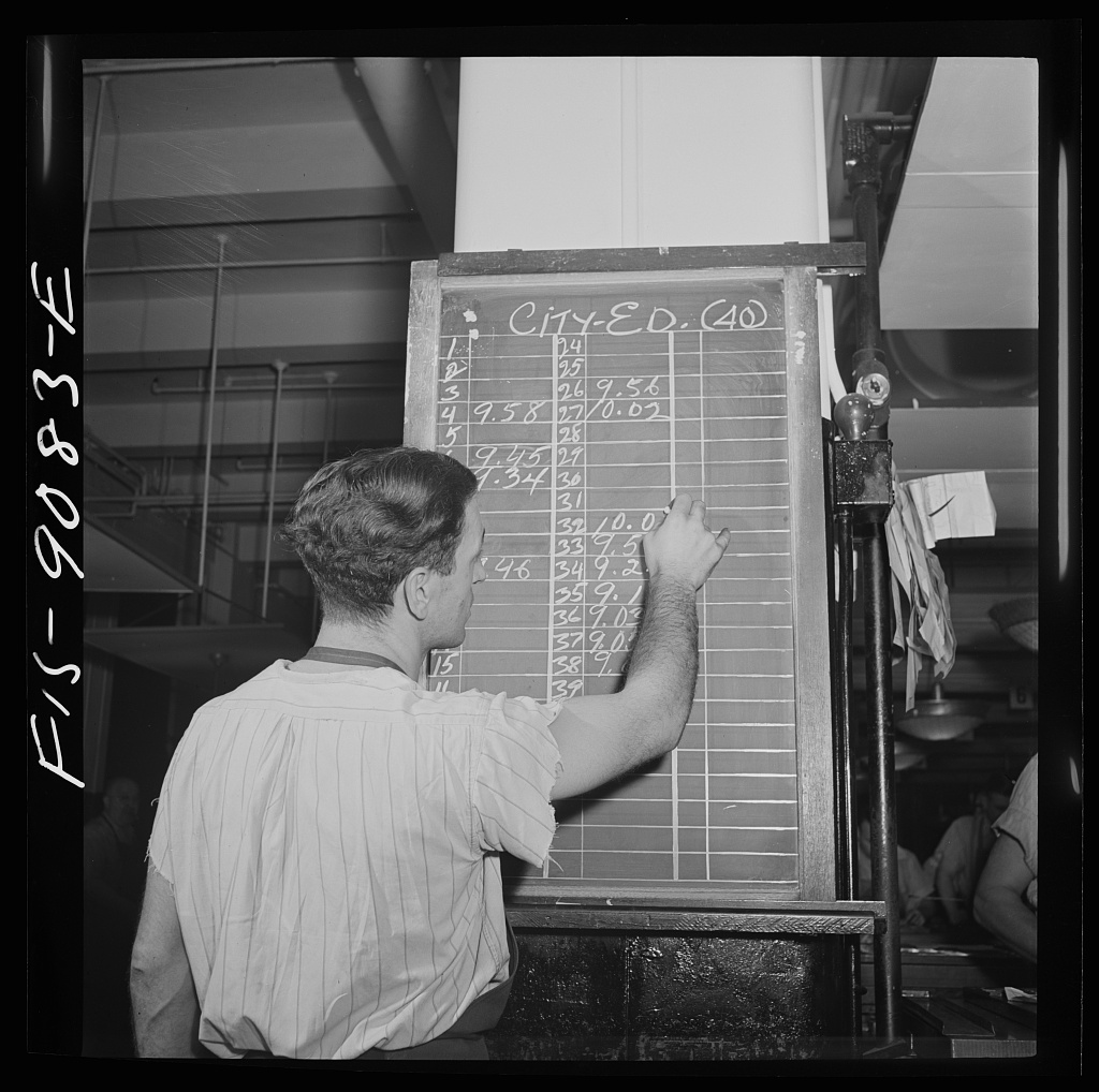 Composing room of the New York Times newspaper. As make-up of each page is completed, time is marked up on board