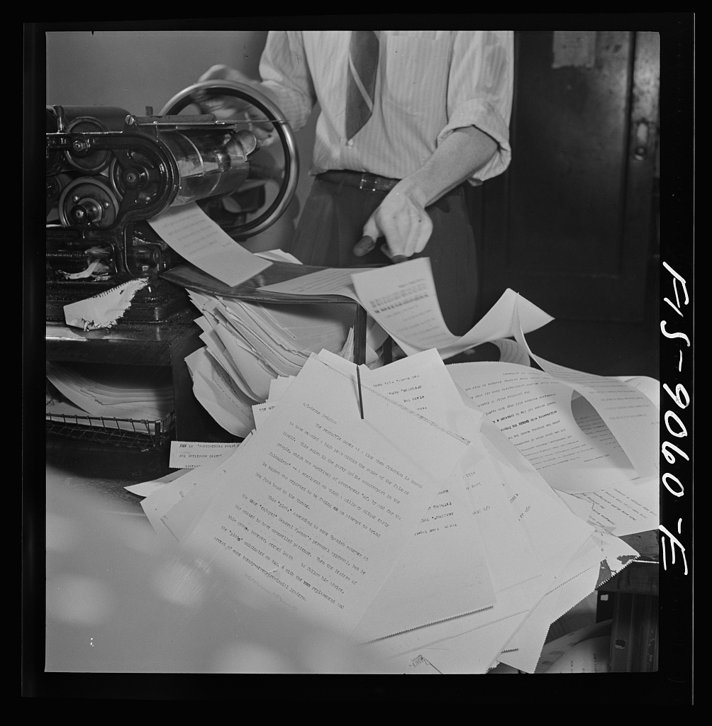 Wire room of the New York Times newspaper. Copy boys mimeograph all incoming dispatches which are then passed through slot into newsroom