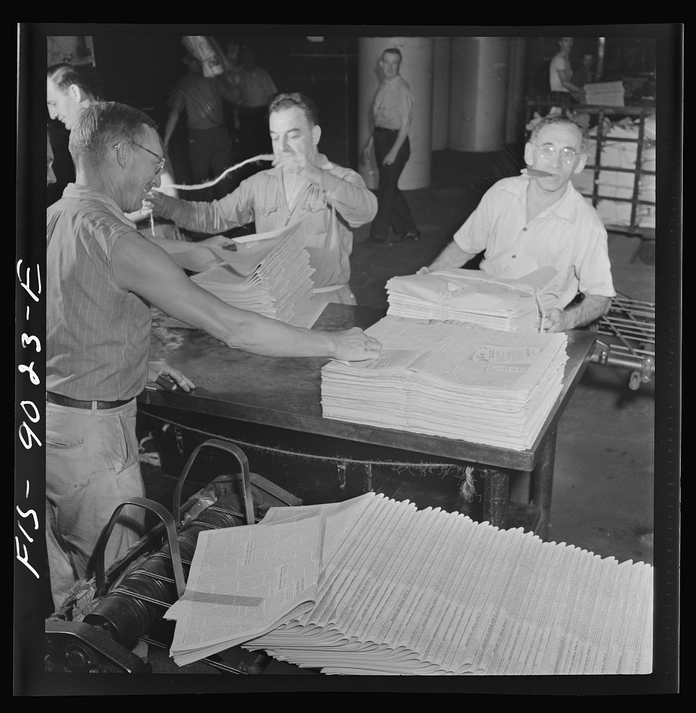 Mailroom of the New York Times newspaper. Papers, delivered from press room on a conveyor, are tied into packages according to orders from retailers
