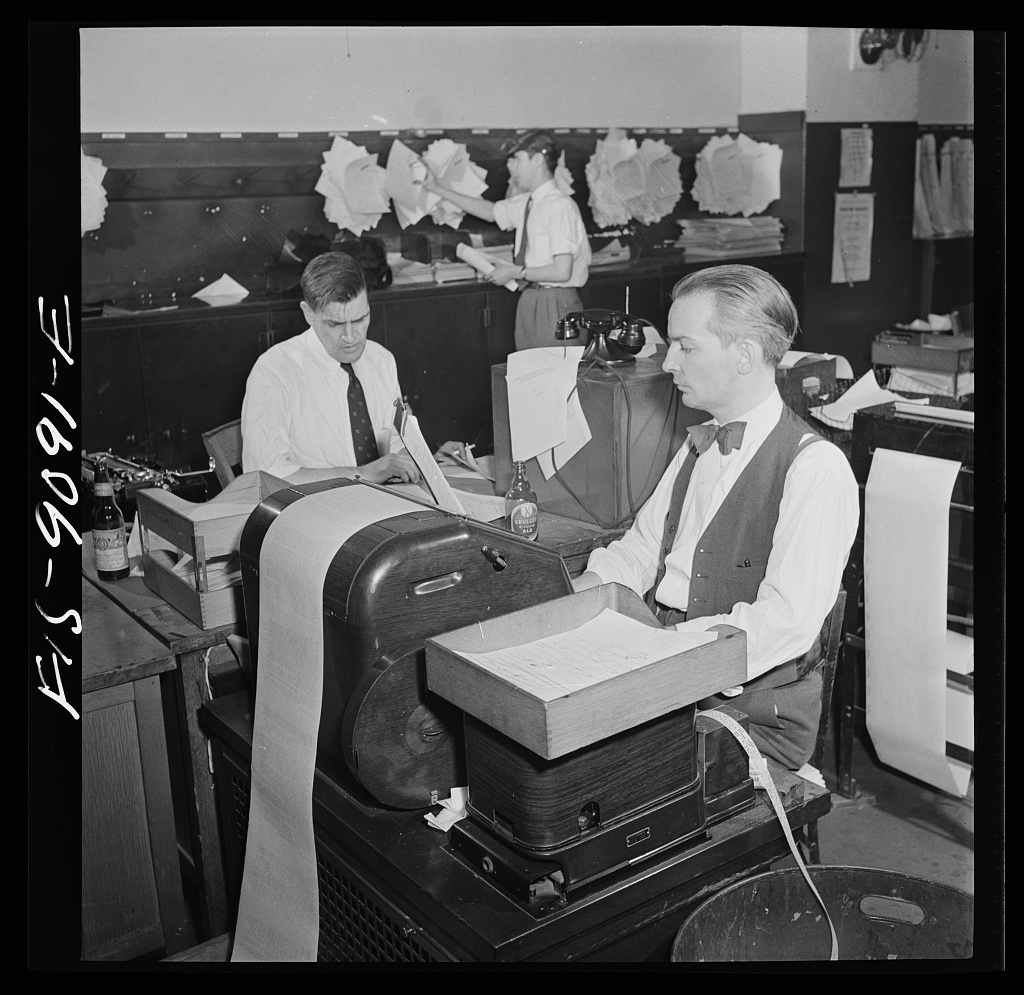 New York Times newspaper syndicate. Correspondents of American newspapers which are syndicate members. In background, copy boy posts Times dispatches