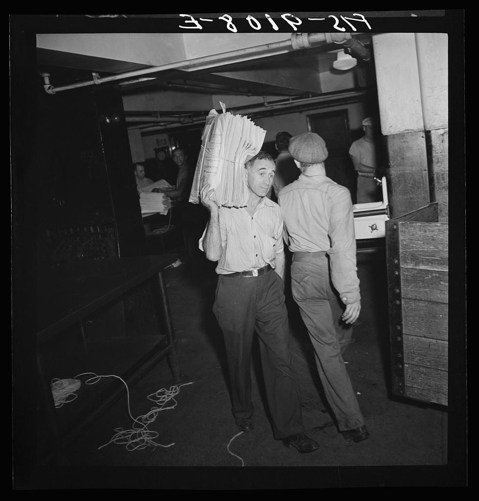 Mailroom of the New York Times newspaper. Bundles of papers are carried to trucks for distribution