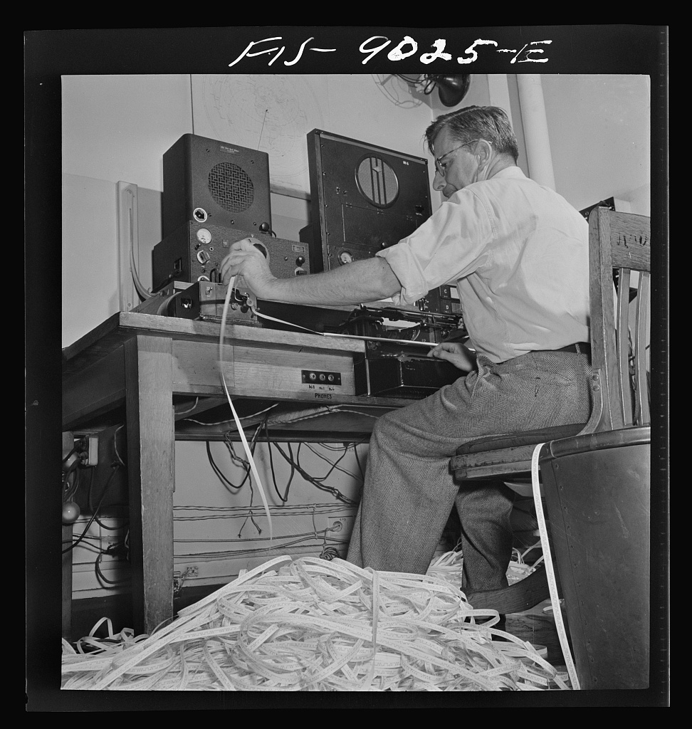 Radio room of the New York Times newspaper. The Times listening post, between 10 and 12 PM, between first and second editions. The operator is listening to Axis news (propaganda) broadcast. Paper in foreground has been previously examined to see what has already been covered in last edition of paper. Operator reports any new angles to city editor. Messages are recorded in tape in international Morse code