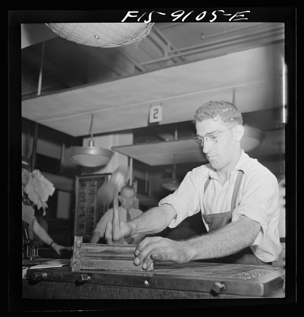 Composing room of the New York Times newspaper. Hammering down type on completely made-up page