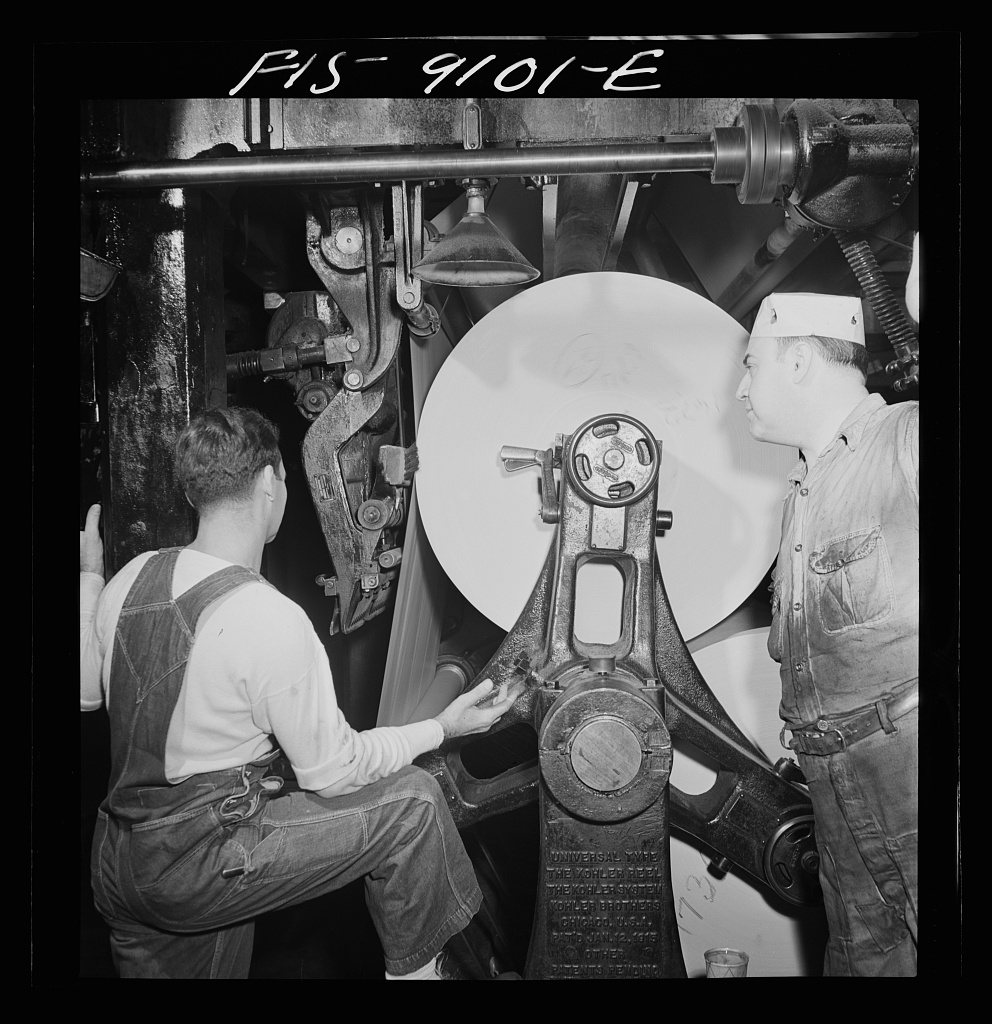 Reel room of the New York Times newspaper. In threading paper through presses two rolls of paper are pasted together by automatic paster so that presses never stop ...
