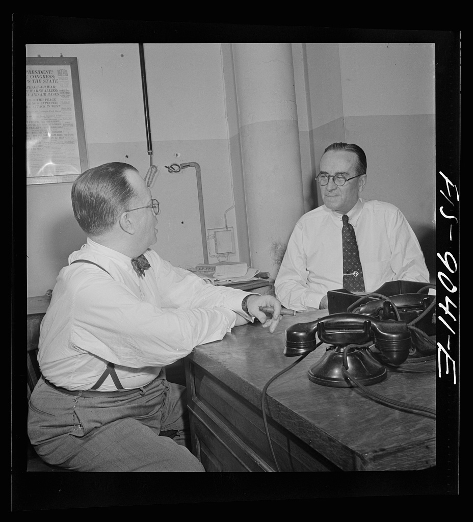 New York, New York. Newsroom of the New York Times newspaper. James and McCaw conferring