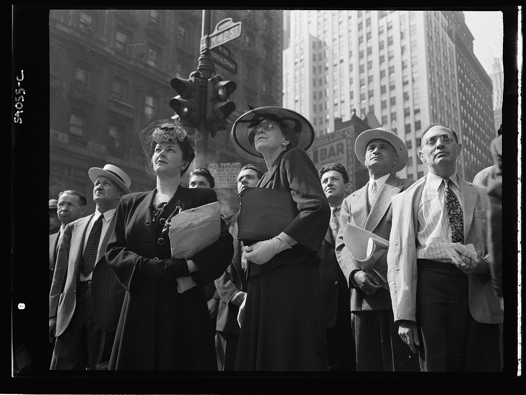 New York, New York. A crowd watching the news line on the Times building at Times Square