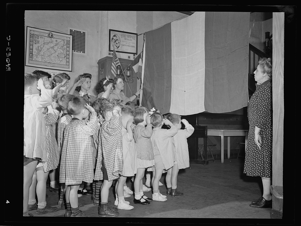 New York, New York. June 6, 1944. Preschool children at L'Ecole maternelle francais on D-day saluting the French flag