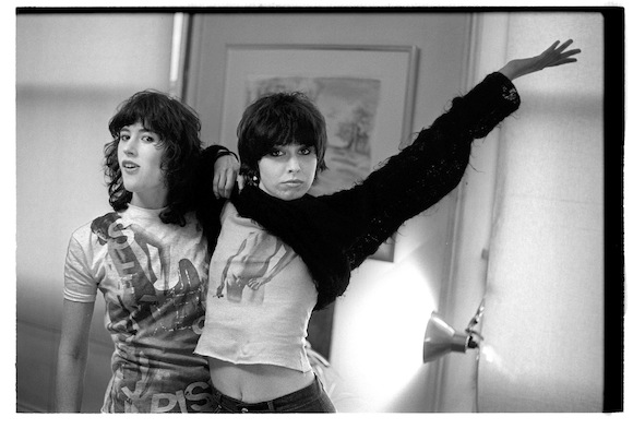Photographer Kate Simon and performer Chrissie Hynde (lifting the front of her mohair jumper from Sex), London, 1976. (c) Joe Stevens