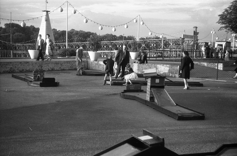 Crazy golf by the embankment in the Festival Pleasure Gardens. Festival Gardens Pier in the background