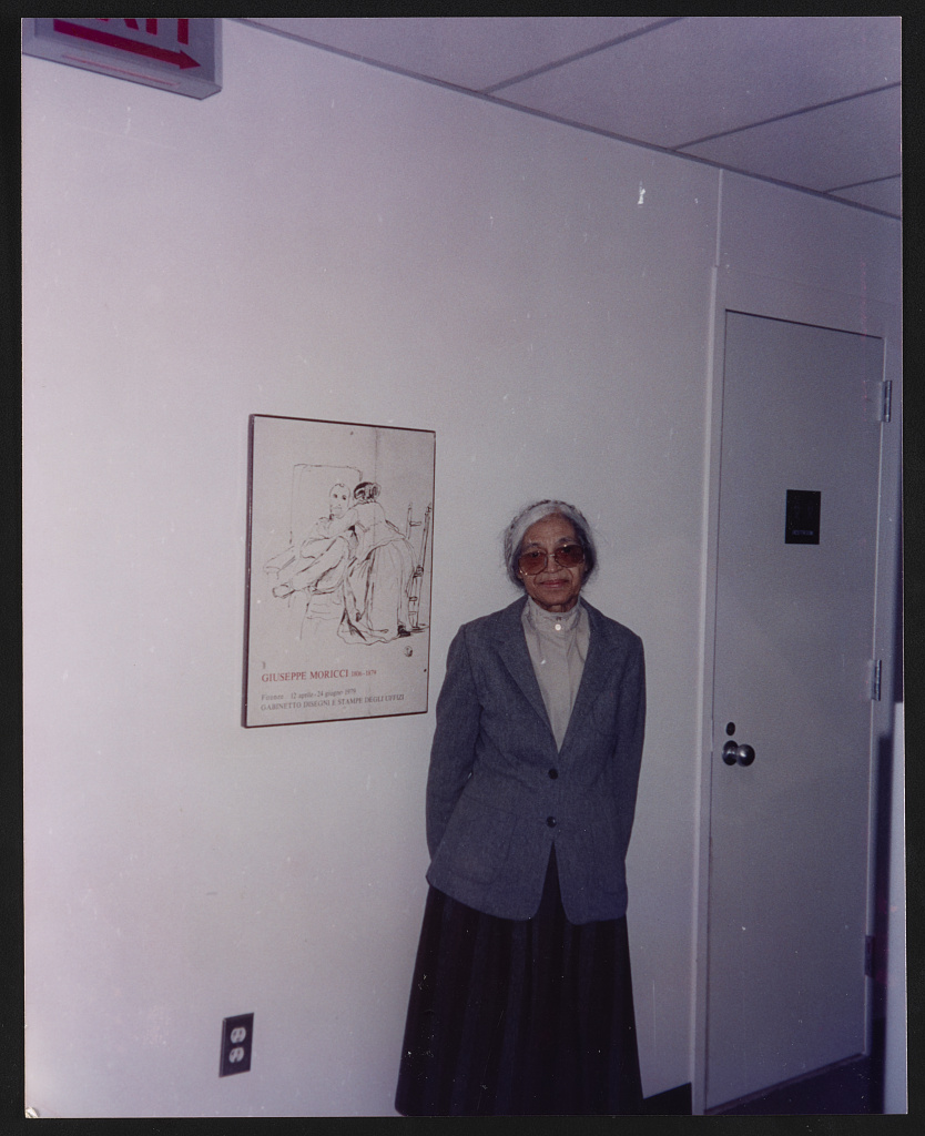 Rosa Parks, full-length portrait, standing next to a Giuseppe Moricci exhibition poster