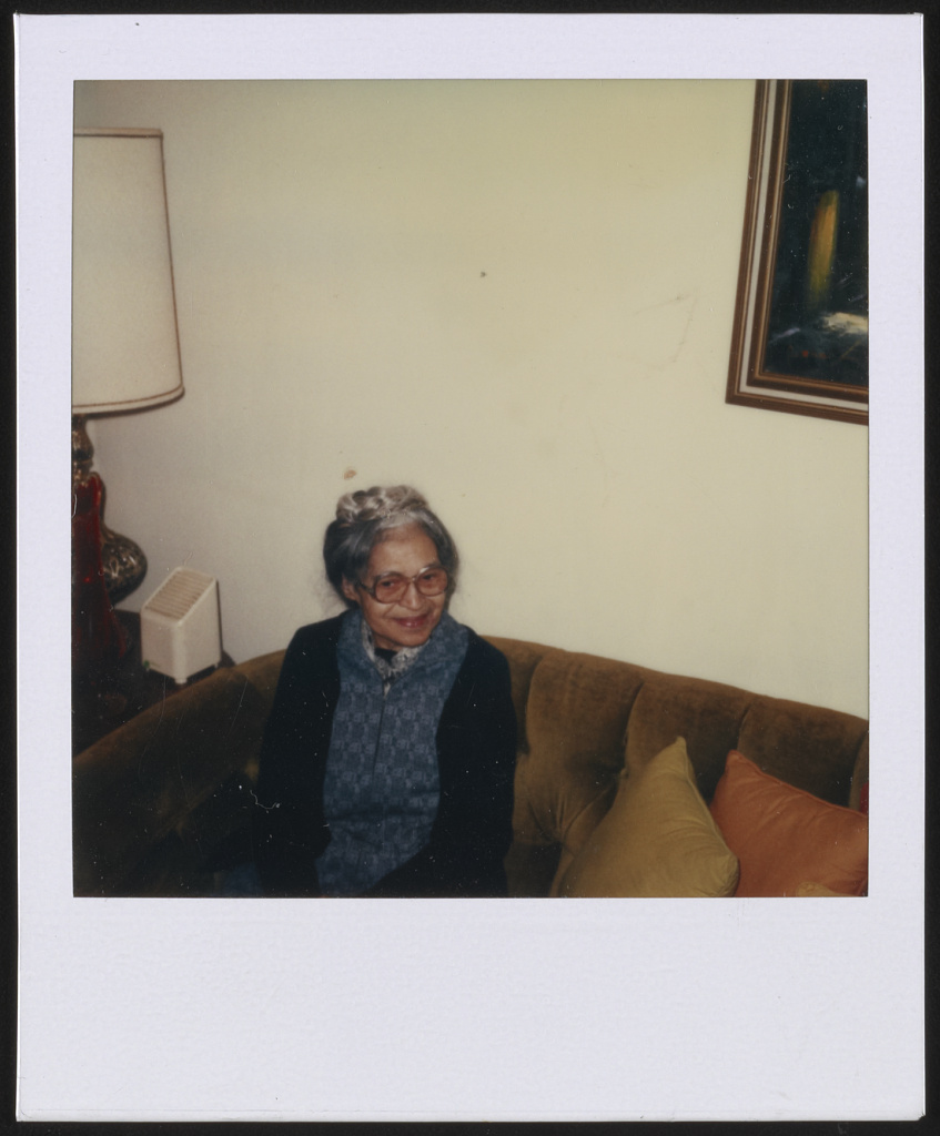 Rosa Parks sitting on a sofa, facing right]