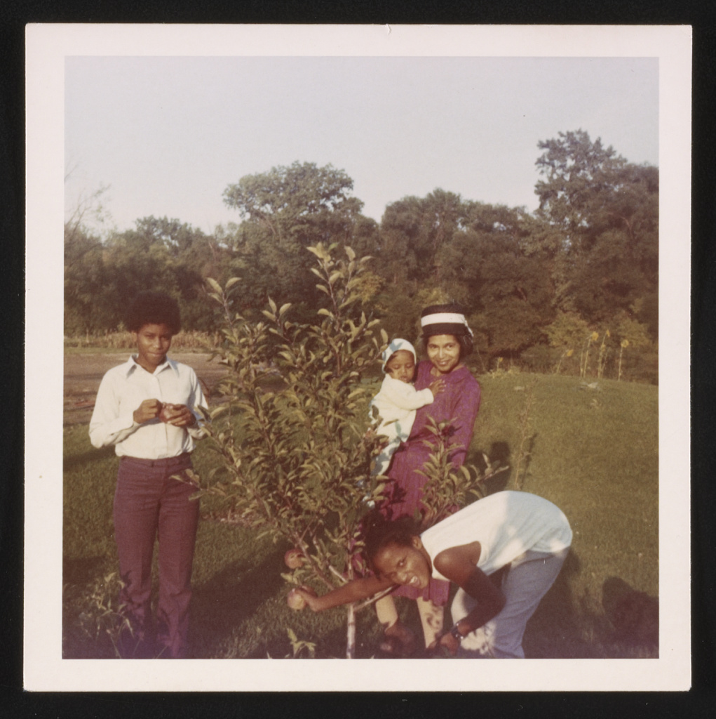 osa Parks standing near an apple tree with three children