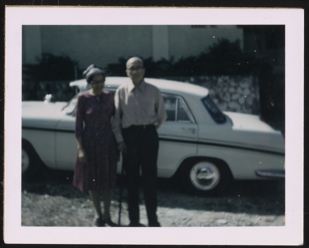 Rosa and Raymond Parks standing in front of a white automobile, likely in Detroit, Michigan May 1970