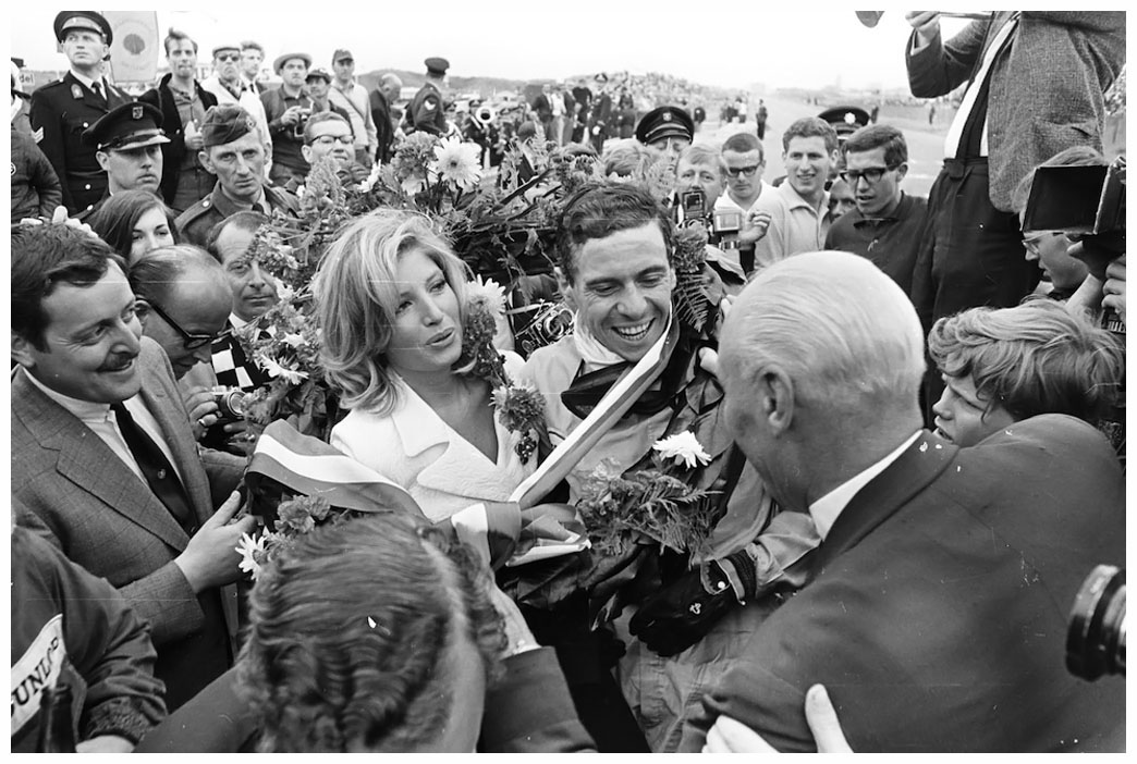 19th July 1965: Scottish racing driver Jim Clark being congratulated by the Italian actress Monica Vitti after winning the Dutch grand prix. (Photo by Victor Blackman/Express/Getty Images)