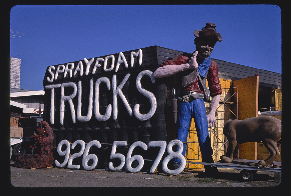 Spray foam trucks prospector statue and sign, overall view, Frontage Road, I-5 1987