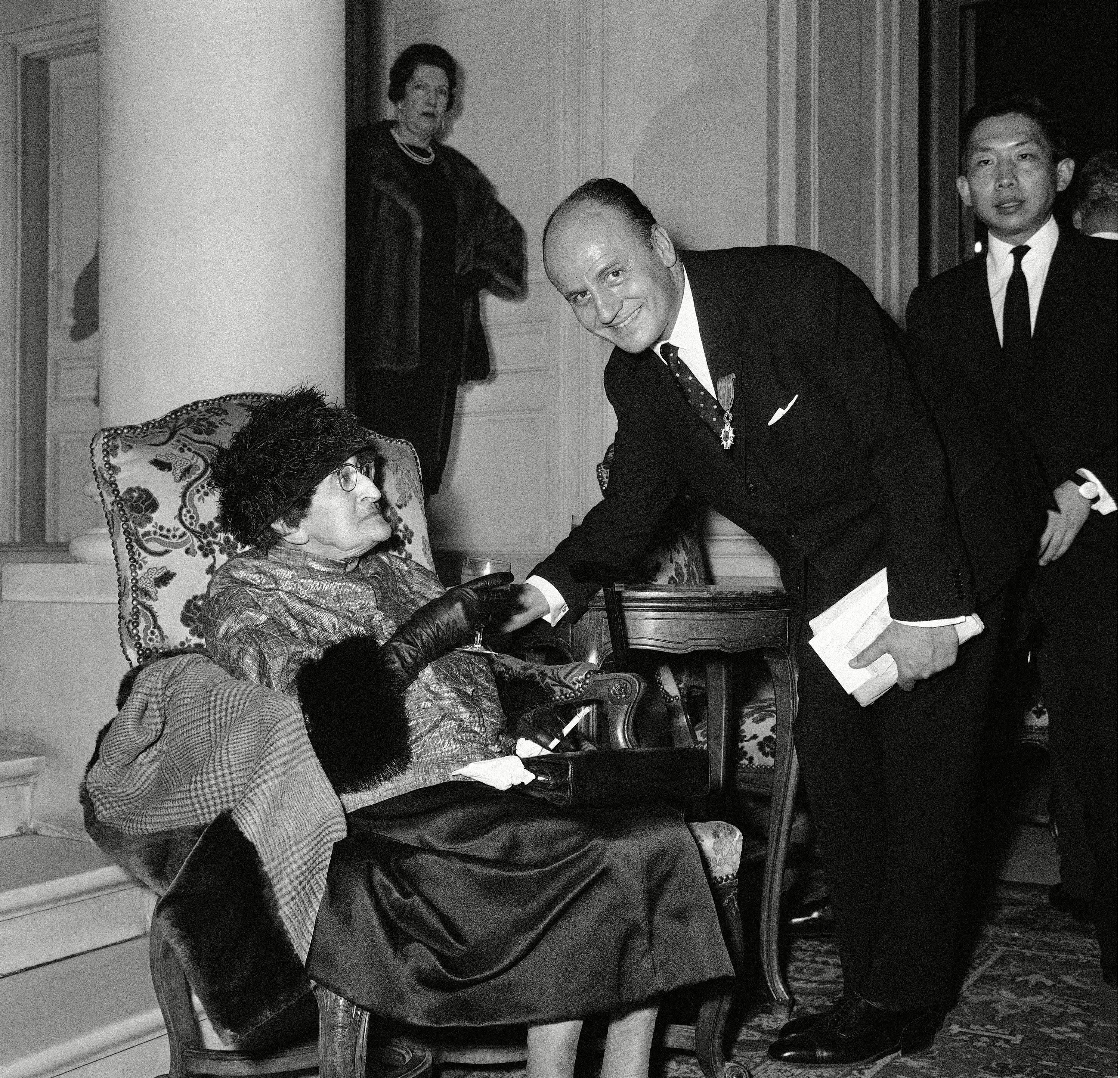 French fashion designer Pierre Balmain shakes hands with American writer Alice B. Toklas after he was awarded the medal of the French Legion of Honor, on by Jean Jacques Guerlain (unseen) at the Ritz Hotel in Paris, France 26 Jan 1962