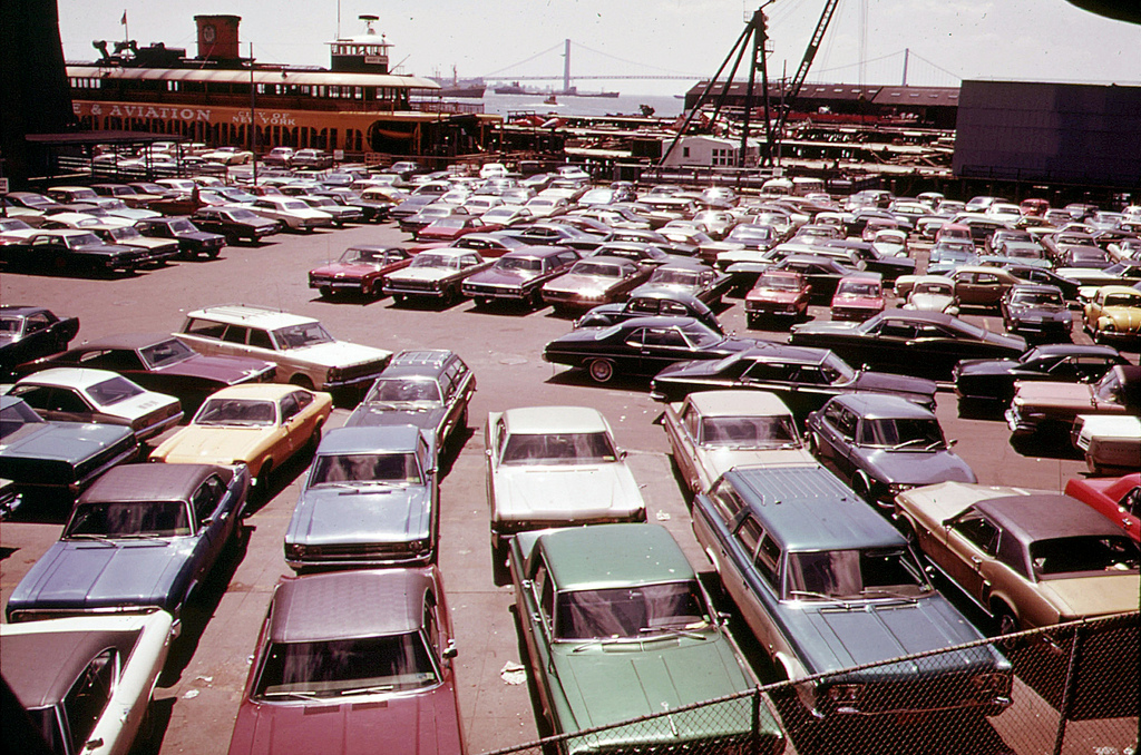 Staten Island Ferry dock on Staten Island, New York. I see a red 1965 Mustang, a purple Dodge station wagon, a Chevy Vega, a bunch of VW Beetles, a Datsun - what can U find? May 1973