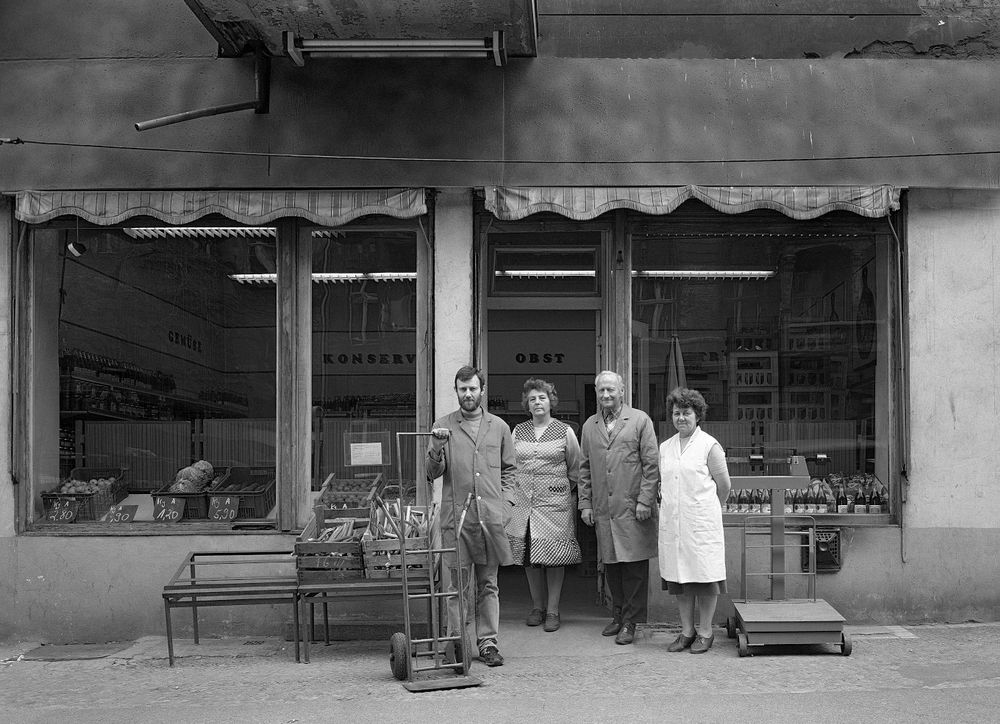 The Schramm family, father, mother and son, and their employee (second from left) in front of their fruit and vegetable shop, No. 3, 1986.