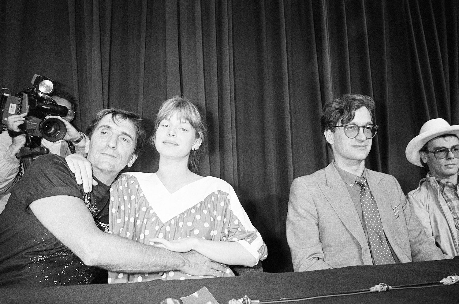 "American actor Harry Dean Stanton and German actress Nastassja Kinski embrace during a photo session at the 37th Cannes Film Festival, . At right are film director Wim Wenders and actor Dean Stockwell. Wenders directed ""Paris, Texas,"" in which Stanton and Kinski star 19 May 1984"