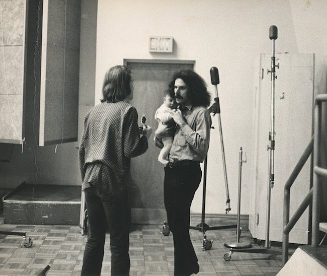In a photo by Bob Cato, photographer Bob Seidemann is seen holding a band member's baby while talking with Big Brother's road manager, David Richards.