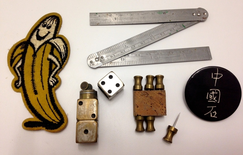 "Just weird cool stuff found in a drawer, including dice-petrol lighter, heavy brass thumb-tacks, folding ruler, smiling-banana patch & a Johnny Thunders ""Chinese Rocks"" badge."