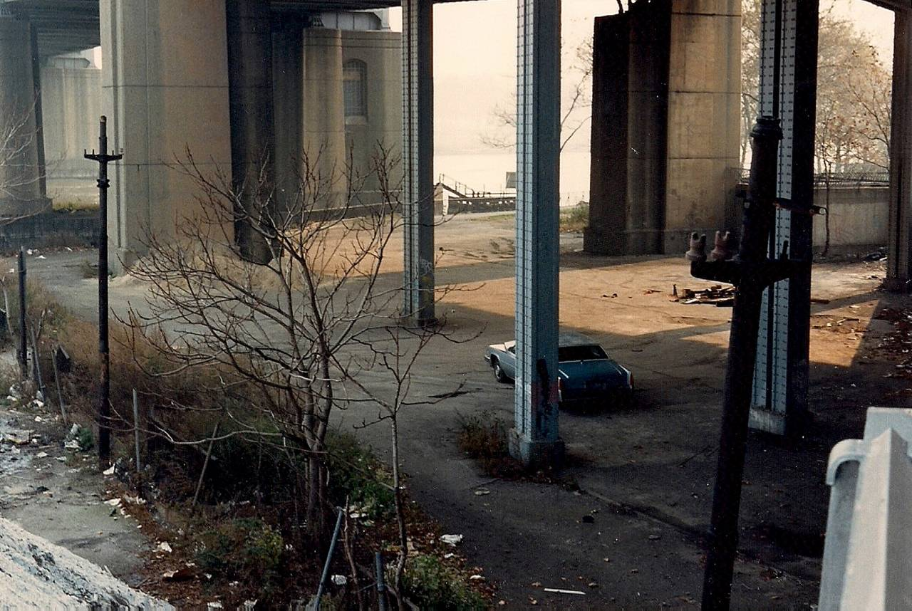 Morning light under one of the bridges crossing the Harlem River from Manhattan to the Bronx. An abandoned, stolen Cadillac awaits. Oct 1982
