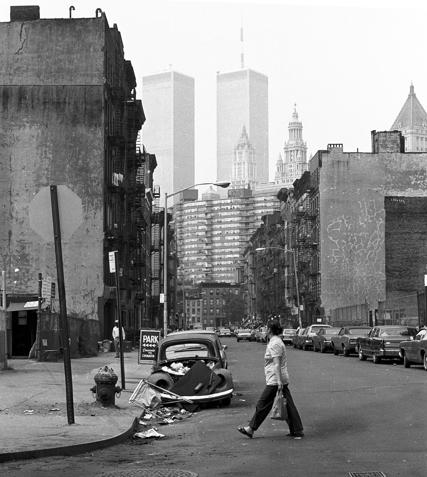 The World Trade Center hovers over unrestored 19th century tenements. Litter fills the street and a stripped Volkswagen Beetle is illegally parked at a fire hydrant. New York. June 1979.