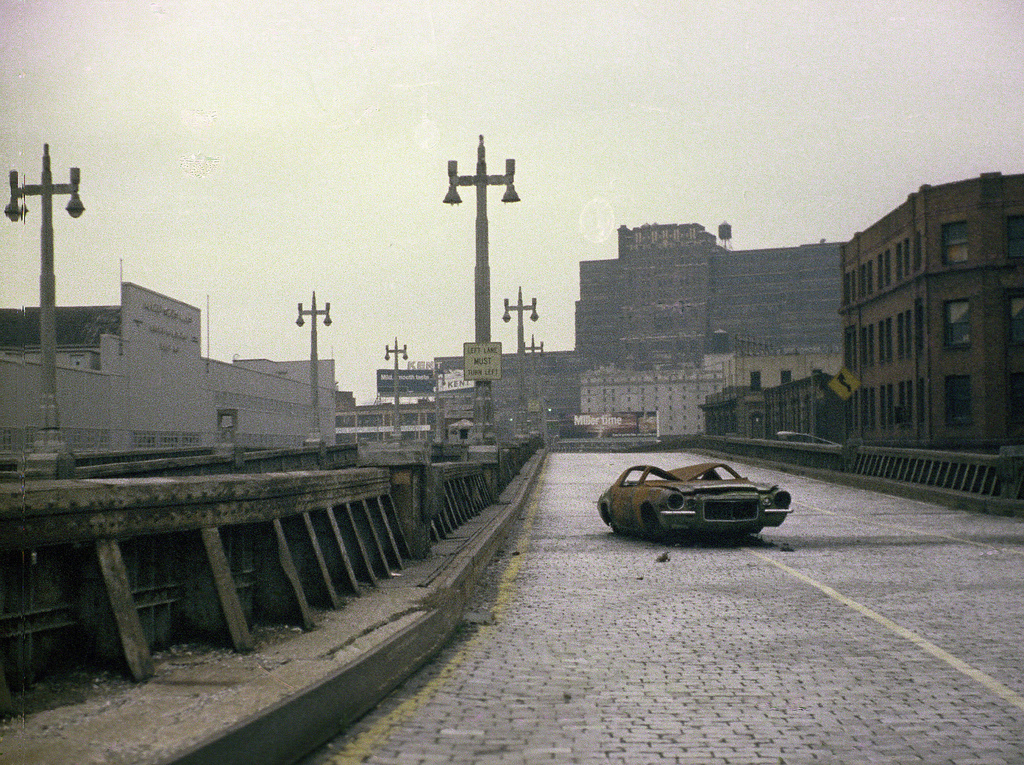 The abandoned West Side Highway with a stolen and burned out 1970s Chevy Camaro. March 1975. New York.
