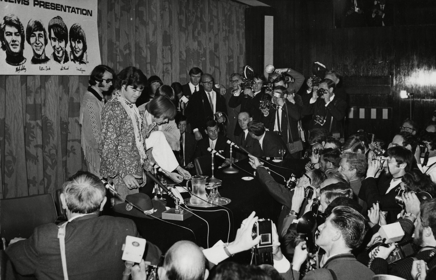 "The U.S. American Pop band The Monkees"", are seen beneath a poster with sketches of themselves, during their press conference in London, England, . The band arrived yesterday and will give their first concert tomorrow at the Empire Pool, here in London England The Monkees 1967, LONDON, United Kingdom England"