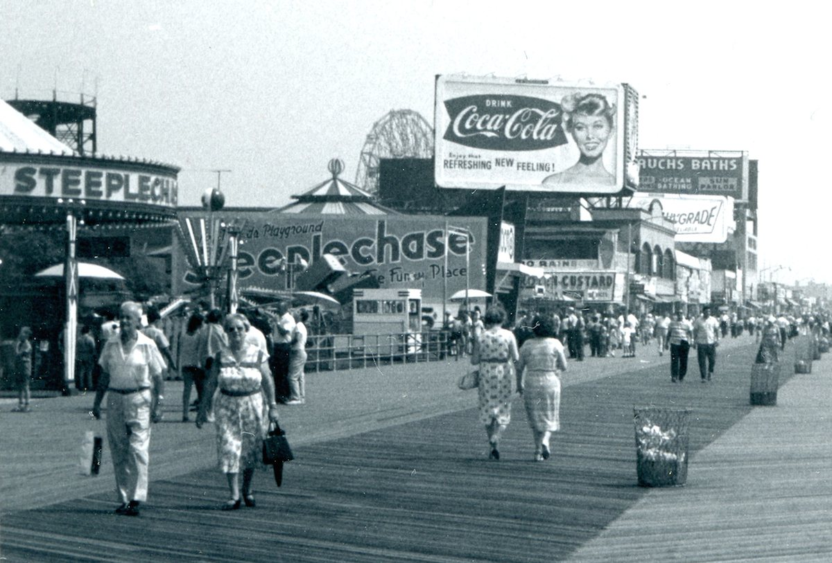 Coney Island 1960sA view looking down the Coney Island boardwalk, along with a cropped closeup of some of the signage. Opened in May 1923, it rises 14 feet above the beach, is 80 feet in width, and stretches for 2.7 miles.