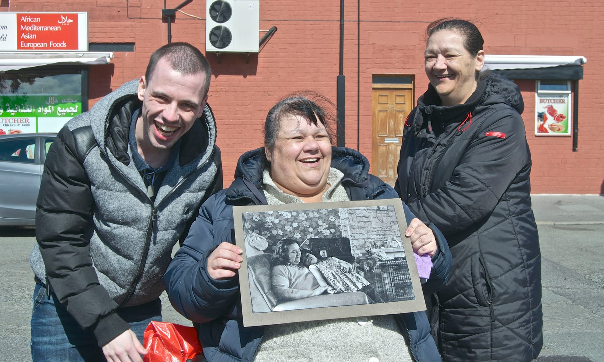 Lizzie, with her son and sister, holds the 1974 picture of her and her mother