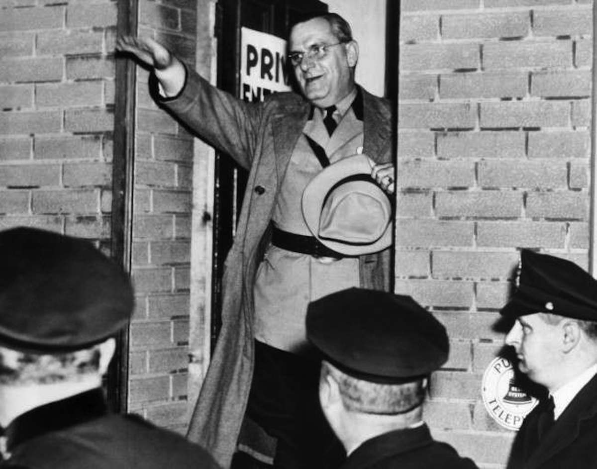"Fritz Kuhn, leader of the German-American Bund, stands in the doorway of a German auditorium at (38th St. and Palisades Ave.) Union City, New Jersey on Oct. 2, 1938 and gives the Nazi salute to his followers. A few minutes later, Kuhn emerged from this same door after a New Jersey crowd, mostly veterans, broke up his ""victory"" meeting, and stoned the leader."