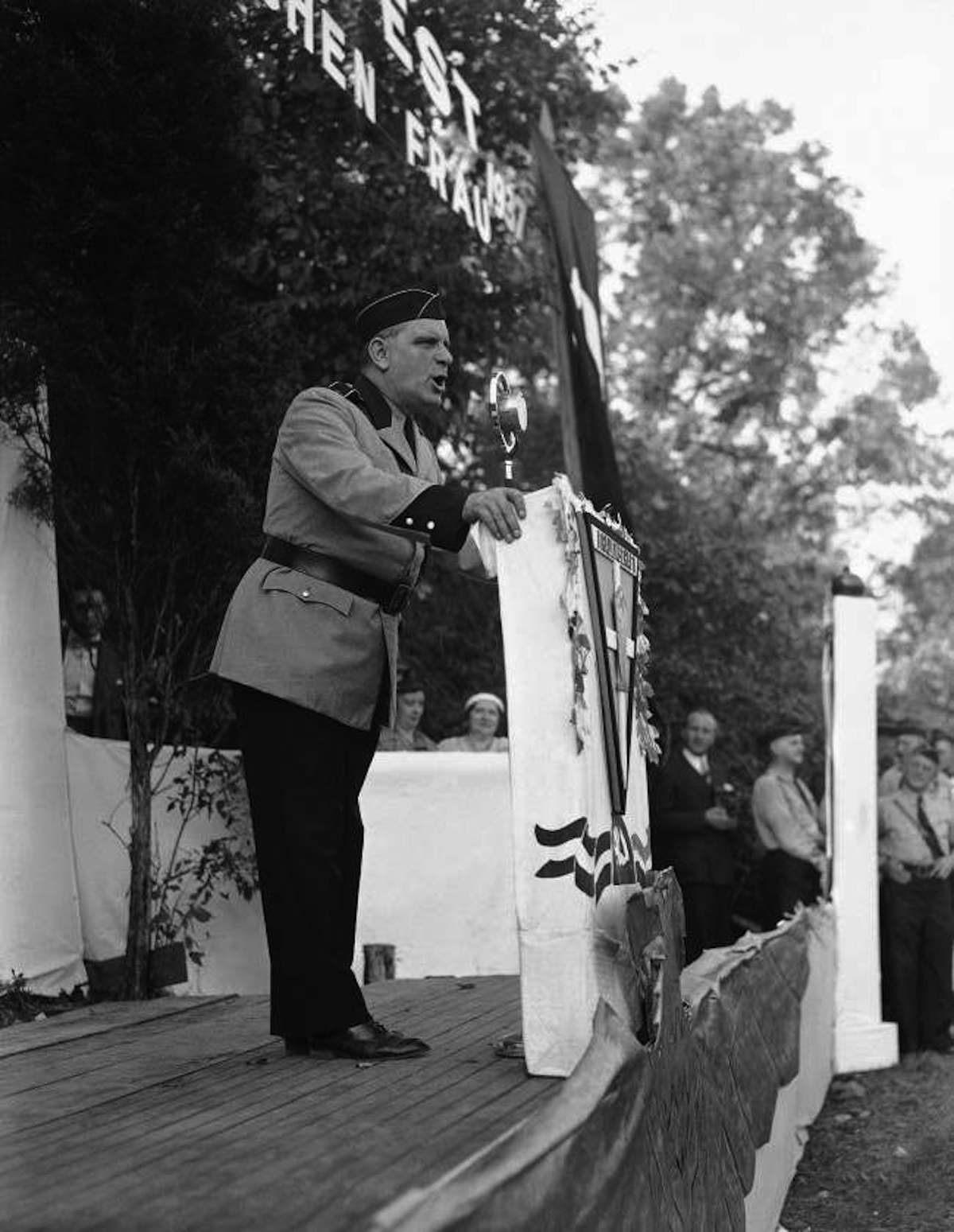 Answering charges that the German-American Volksbund is engaged in un-American activity, Fritz Kuhn, above, told thousands gathered camp Nordland, Andover, New Jersey on Sept. 26, 1937, the groups' activities are founded on patriotic lines. He said the bund will continue its fight for Americanism until America is controlled by Americans and by a bunch of Russian-controlled Jews. American flags outnumbered swastikas, but there was goose stepping and Nazi saluting