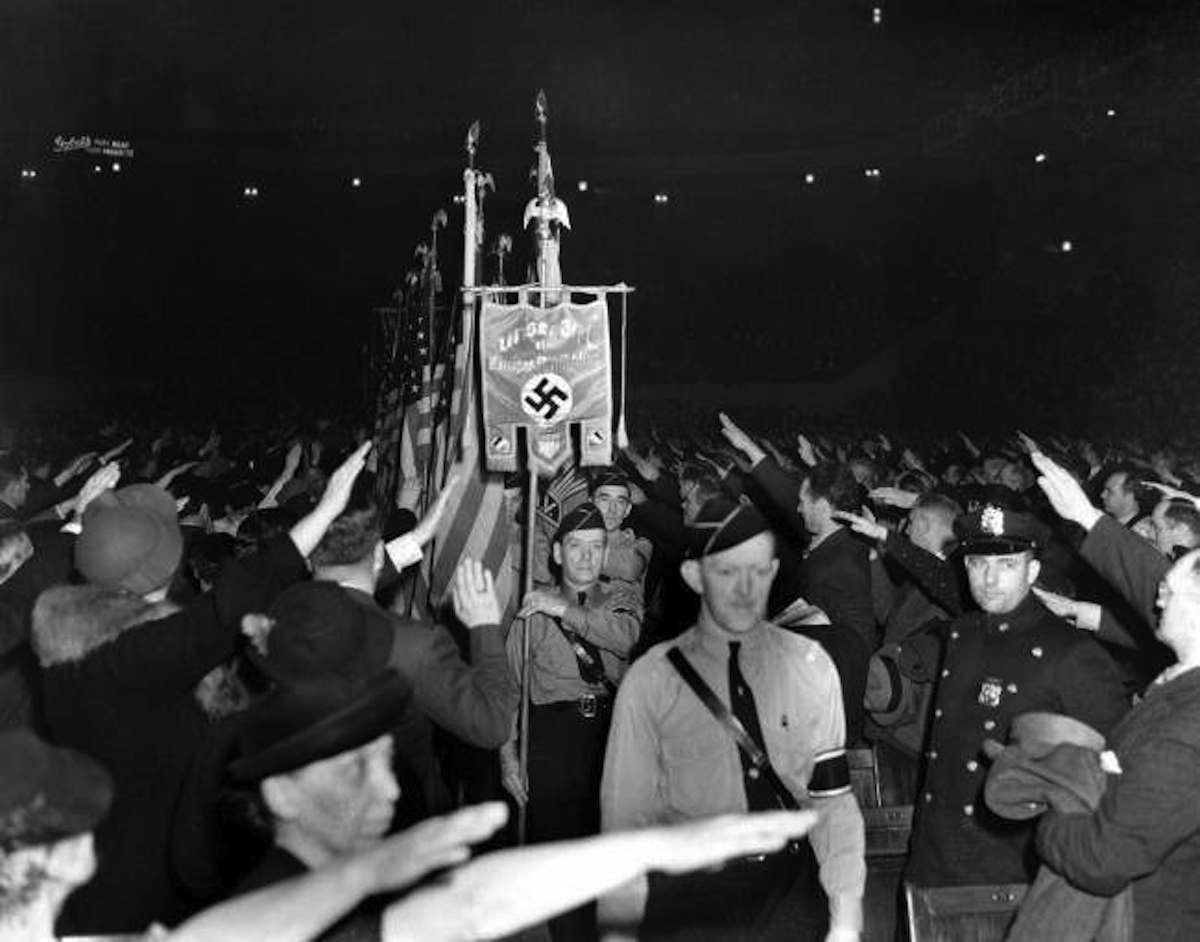 The crowd responds with a Hitler salute as uniformed members of a German-American Bund color guard march at a gathering in New York's Madison Square Garden, Feb. 20, 1939.