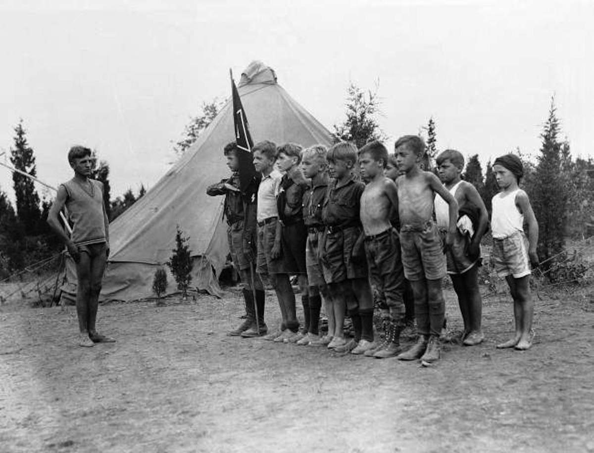 Hans Schult, left, a leader at Camp Wille und Macht near Griggston, New Jersey, puts a group of German boys between the ages of 8 and 16 through a drill before a meal. The camp, flying the Nazi flag, is sponsored by Friends of the New Germany, and contains 200 boys from New York, Brooklyn, Buffalo, and Philadelphia. Date: 09/08/1934