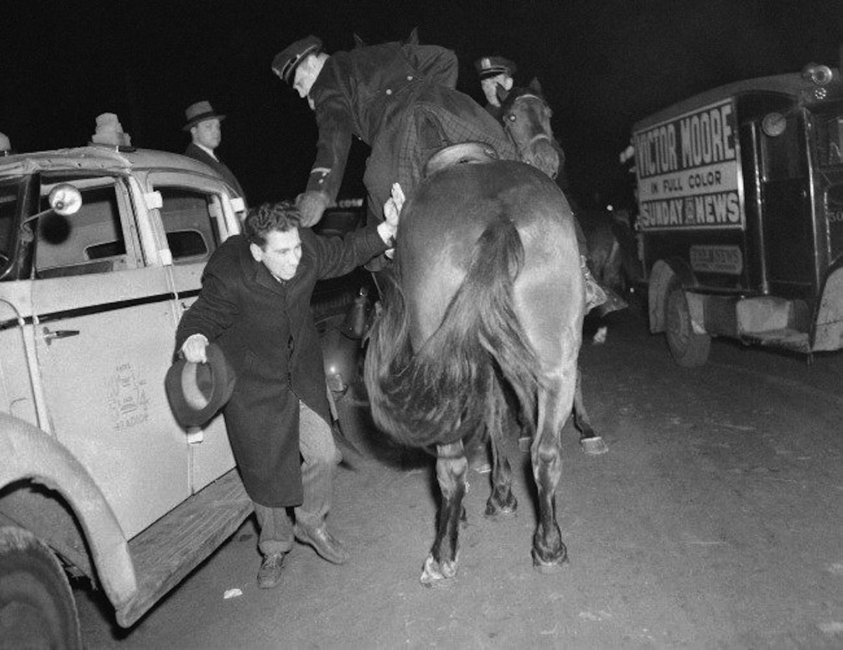 A mounted policeman strikes with the back of his gloved hand at an unidentified man near Madison Square Garden, New York, during the German American Bund rally Feb. 20, 1939. A force of 1,500 policemen were stationed in and around the Garden to forestall anti-Bund demonstrations.