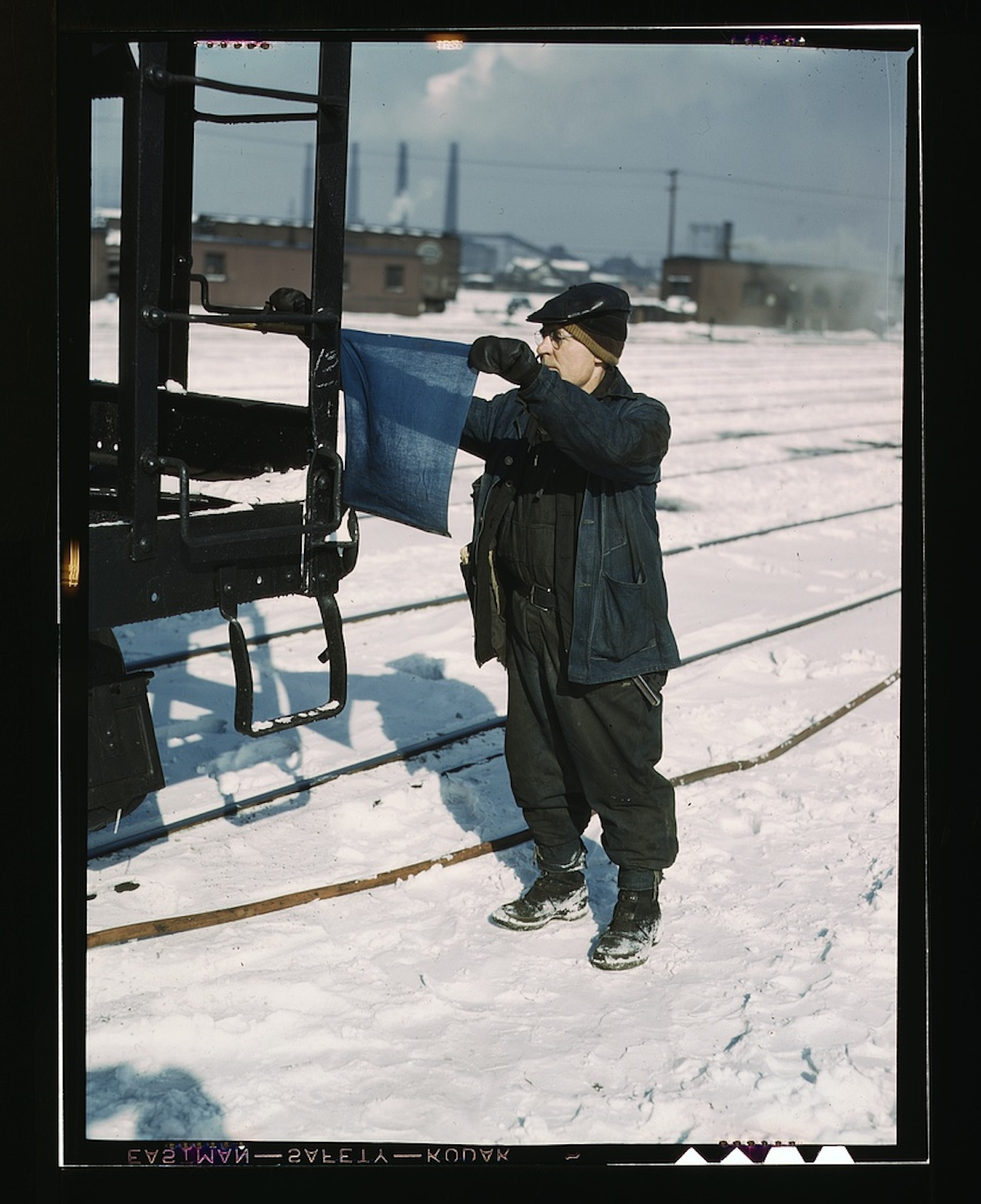 John Paulinski, car inspector, blue flagging a train for inspection, at Corwith yard, Santa Fe RR trip, Chicago, Ill. 1 transparency : color. Contributor: Delano, Jack Date: 1939