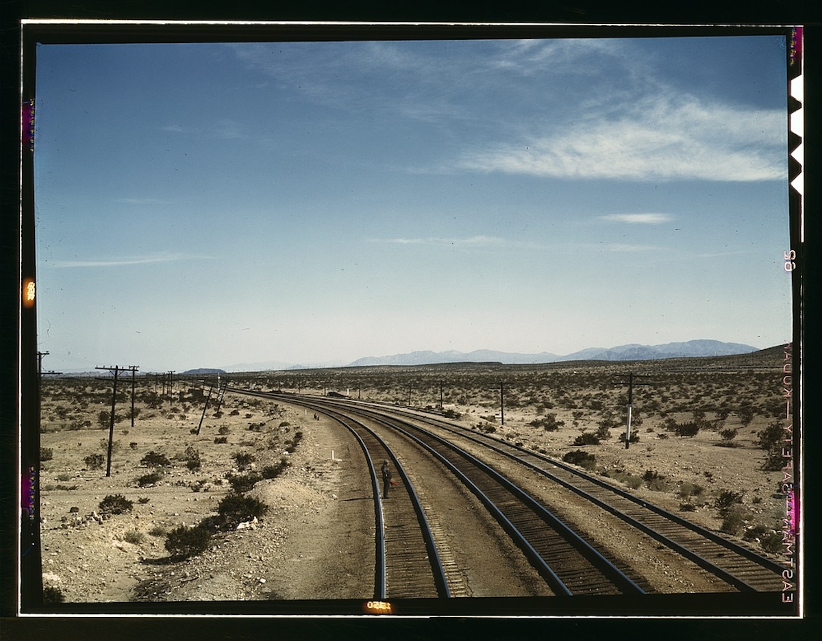 Flagman standing at a distance behind a Santa Fe R.R. west bound freight train during a stop, Bagdad, Calif. 1 transparency : color. Contributor: Delano, Jack Date: 1939