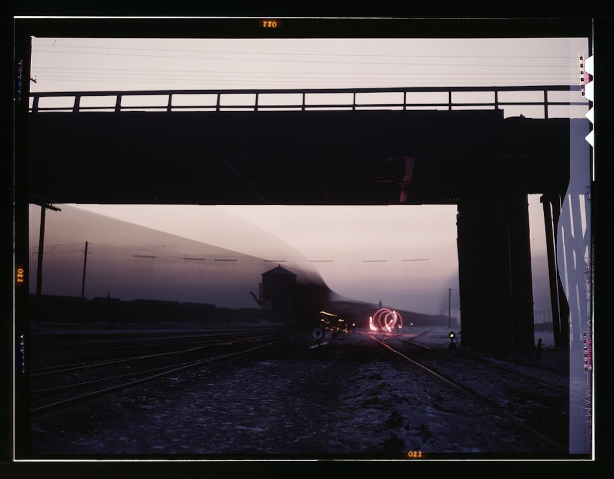 View in a departure yard at C & NW RR's [i.e. Chicago and North Western railroad's] Proviso (?) yard at twilight, Chicago, Ill. Brakeman is signaling with a red flare and the ... 1 transparency : color. Contributor: Delano, Jack Date: 1939