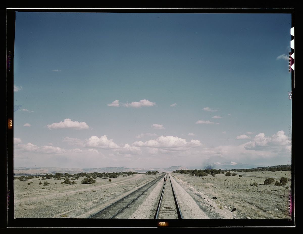 Flagman standing behind his train to flag oncoming trains at a small siding between Laguna, N[ew] Mex[ico] and Gallup, N[ew] Mex[ico]. Sant Fe R.R., Santa Fe trip 1 transparency : color. | Photograph shows train and flagman in far distance. Contributor: Delano, Jack