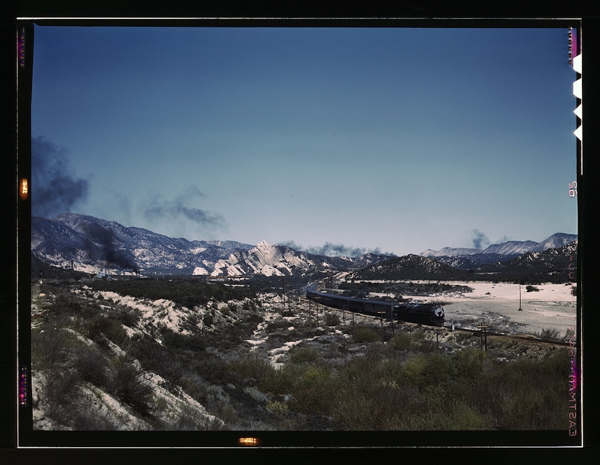 "Santa Fe R.R. trains going through Cajon Pass in the San Bernardino Mountains, Cajon, Calif. On the right, streamliner ""Chief"" going west; in the background, on the left, a freight train with ... 1 transparency : color. Contributor: Delano, Jack Date: 1939"
